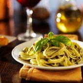 italian fettuccine in basil pesto sauce on dinner table at night