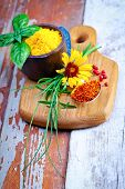 Colourful dried ground spices in bowls spilling onto an old aged scored wooden surface