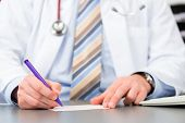 Young doctor writing medical prescription in surgery at desk