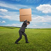 tired young businessman carrying two heavy boxes at outdoor