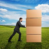 smiley businessman moving boxes on the grass at outdoor