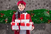Smiling woman holding large presents against snowflake wallpaper pattern