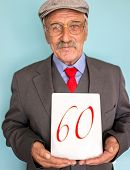 Portrait of a smiling and confident elderly good looking business man holding card with sixties number