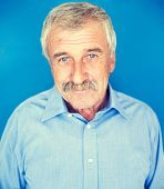 Confident elderly good looking man on blue wall