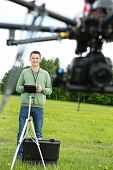 Young male engineer flying UAV octocopter with remote control in park