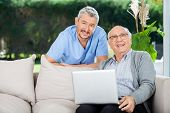 Portrait of happy male nurse and senior man with laptop on couch at nursing home porch