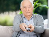 Portrait of senior man using remote control while sitting on couch at nursing home porch