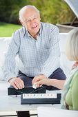 Happy senior man playing rummy with woman at nursing home porch