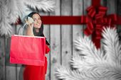 Woman standing with shopping bag against blurred snowflakes on planks