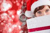 Woman holding a christmas present against blurred christmas background