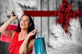 Woman standing with shopping bags against festive bow over wood