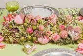 Beautiful twotone flower arrangement in soft pink and green on a christmas dinner table