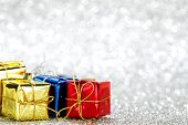 Holiday gifts in colorful boxes on silver bokeh background