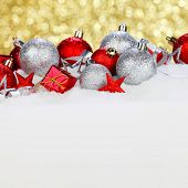 Christmas card with beautiful decorations in snow on golden background