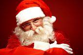 Smiling Santa Claus in eyeglasses posing for camera