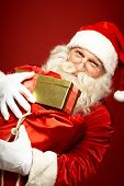 Portrait of cheerful Santa Claus holding huge sack full of gifts