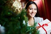 Portrait of smiling businesswoman with xmas giftbox looking at camera