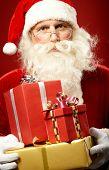 Serious Santa Claus with giftboxes looking at camera