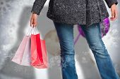 Smiling woman holding shopping bag against blurred christmas decorations