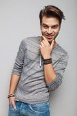 Smiling young fashion man holding one hand in pocket while fixing his beard.
