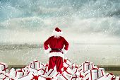 Santa standing on pile of gifts against coastline city