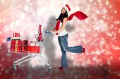 Woman standing with shopping trolley against blurred lights