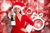 Woman holding a champagne bottle against blurred christmas background