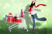 Woman standing with shopping trolley against green abstract light spot design