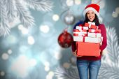 Woman holding many christmas presents against baubles hanging over christmas scene
