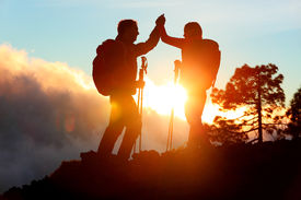 picture of mountain-high  - Hiking people reaching summit top giving high five at mountain top at sunset - JPG