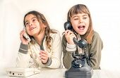 image of 7-year-old  - Two seven year old girls talking on the old vintage phones with the white background - JPG