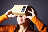 pic of experiments  - Color shot of a young woman looking through a cardboard a device with which one can experience virtual reality on a mobile phone - JPG