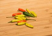 stock photo of cayenne pepper  - Green and orange jalapeno and cayenne peppers on a wood cutting board - JPG