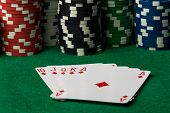 picture of flush  - diamonds straight flush with poker chips on green table