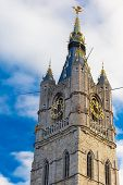 stock photo of gents  - View from the bottom up to the tower Belfry with a clock and a statue of a dragon in Ghent - JPG