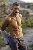 foto of undressing  - Athlete with a strong body undressing looking at nature background - JPG