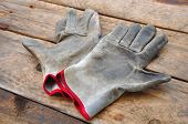 picture of dirty  - Old safety gloves on wooden background - JPG