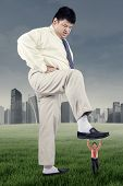 stock photo of big-foot  - Business competition concept with big businessman trample a little entrepreneur - JPG