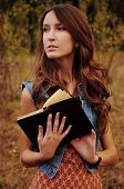 pic of auburn  - cute young woman with long auburn hair in the autumn forest reading a book - JPG