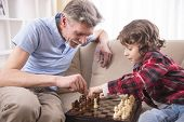 stock photo of grandfather  - Young boy is playing chess with his grandfather at home - JPG