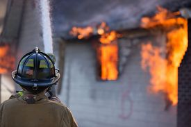 stock photo of firemen  - A fireman pours a stream of water on a burning home - JPG