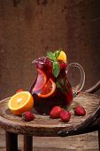 image of jug  - Wine of Sangrija in a transparent jug on a wooden table with an orange and a strawberry - JPG