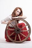 stock photo of wagon wheel  - young woman with an old wagon wheel on white background - JPG