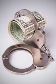 stock photo of punishment  - economic crime the punishment of the offender roll of dollars in handcuffs vertical composition DSLR photography finance and law moneys of the United States - JPG