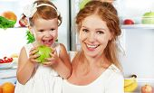 stock photo of refrigerator  - happy family mother and child baby daughter around the refrigerator with healthy food fruits and vegetables - JPG