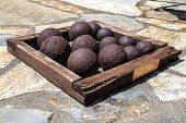 stock photo of cannon-ball  - Many of historical old cannon balls heap of iron rusty balls - JPG