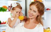 foto of refrigerator  - happy family mother and baby daughter drinking orange juice in the kitchen near the refrigerator - JPG