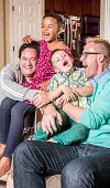 stock photo of tickling  - Gay parents in the living room laugh with their children - JPG