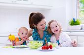 foto of cook eating  - Young mother and two children cooking in a kitchen - JPG
