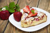 stock photo of devonshire  - Homemade pie with fresh strawberries on a plate on a wooden table - JPG